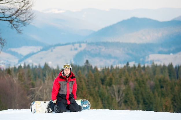 スノーボーダーのスキー場で休んで、ひざまずいて、美しい山と森、冬のスポーツコンセプトの背景にカメラを見て