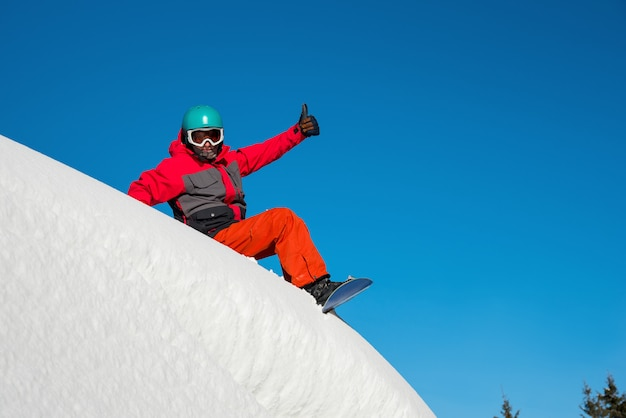 Snowboarder resting on top of the mountain