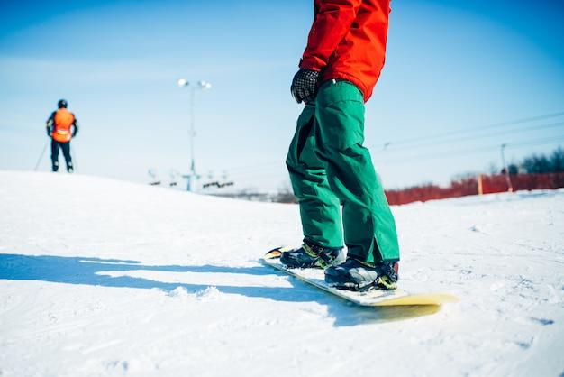 雪の丘に乗るスノーボーダー。冬のエクストリームスポーツ、アクティブなライフスタイル。山でのスノーボード