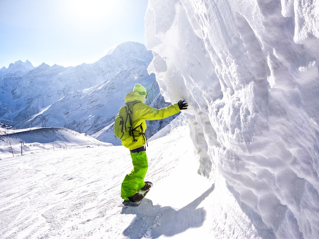 Snowboarder riding along ice wall in ski resort at mountain