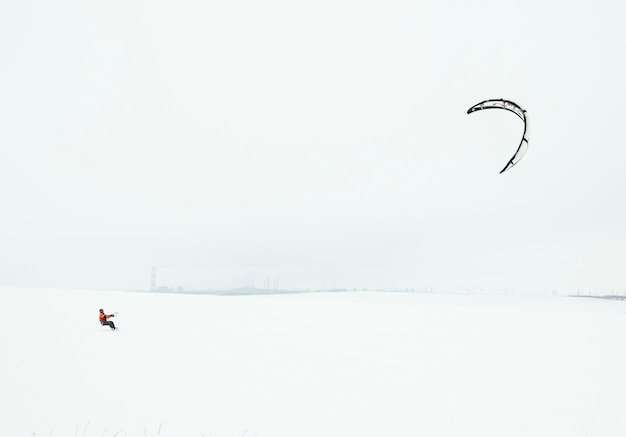 Snowboarder riding a kite on a background of an industrial enterprise