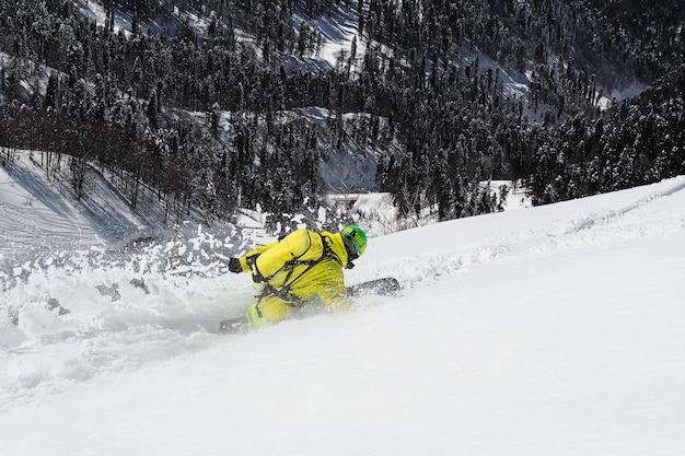 森の背景でパウダーに乗ってスノーボーダー。冬のエクストリームスポーツ