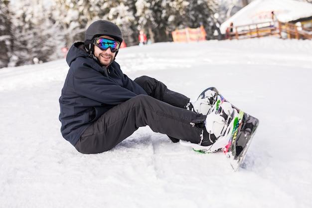 스노 보더는 슬로프 가장자리의 산에 높게 앉아 라이딩하기 전에 카메라를 바라 봅니다.