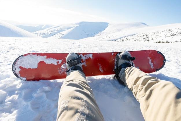 프랑스 알프스 스키 리조트에서 일몰의 휴식 시간에 앉아 있는 스노보더 - 산 꼭대기에 있는 사람이 타고 내릴 준비가 된 겨울 스포츠 개념 - 따뜻한 백라이트 필터가 있는 다리 전망