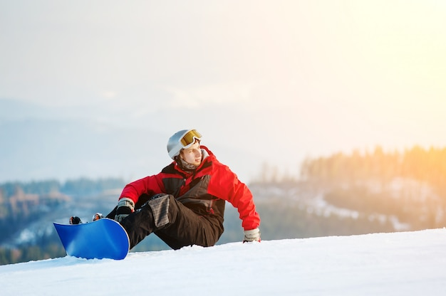 Snowboarder sitting on snowy slope on top of a mountain