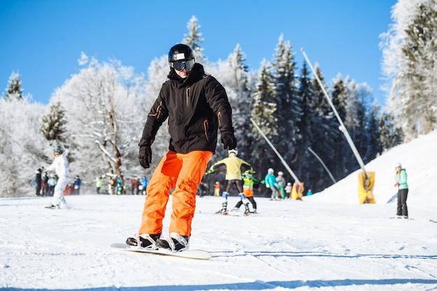 Сноубордист на коньках в горах с синим небом