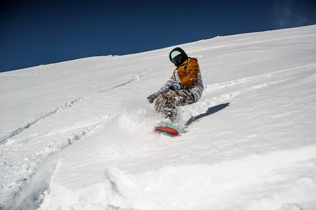 Snowboarder in sportswear riding on the powder mountain slope