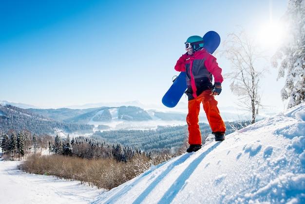 Сноубордист, стоя на вершине горы, глядя в сторону, отдыхая после катания