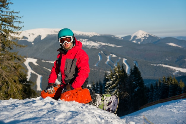 Snowboarder on top of slope in winter evening