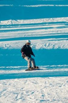 Сноубордист в шлеме и очках спускается с холма в зимнем белом пейзаже