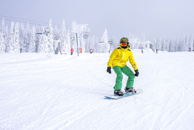 Snowboarder in a yellow and green costume riding down the slope with a ski lift in the