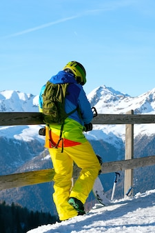 A snowboarder in yellow pants and a colorful jacket stands on the observation deck and repairs the board. people sport concept