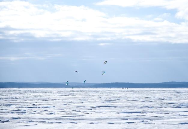 낙하산을 타는 스노 보더들은 얼어 붙은 호수를 타고 올라갑니다.