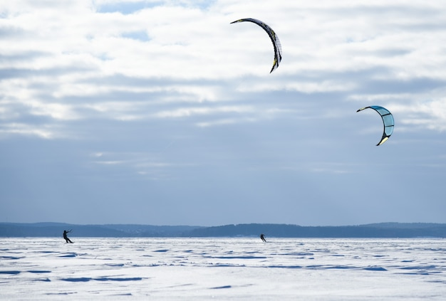 パラシュートでスノーボーダーが凍った湖に乗ります。