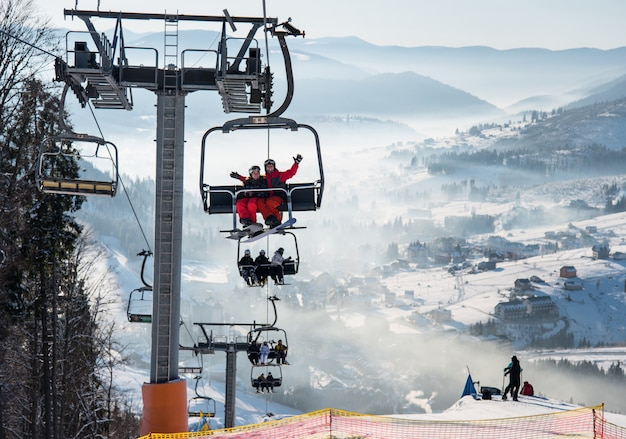 Snowboarders and skiers on a ski lift at winter ski resort with beautiful background of snow-covered slopes, forests, hills