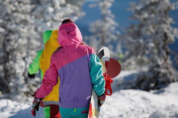 Сноубордисты гуляют по пушистому снегу в зимнем хвойном лесу. на них лыжная одежда: комбинезоны с капюшонами. вид сзади. здоровый образ жизни. спортивная концепция. выборочный фокус.
