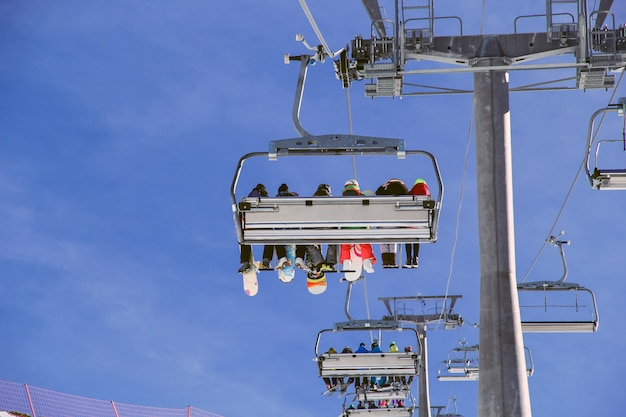 Snowboarders with equipment going up with chairlift