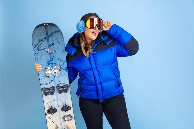 スノーボード。青いスタジオの背景に白人女性の肖像画。暖かい服を着た美しい女性モデル。感情、表情、販売、広告の概念。冬の気分、クリスマスの時期、休日。