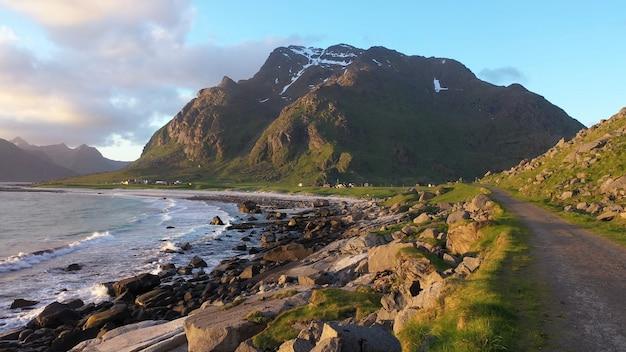 岩の多い海岸の雪をかぶった山は青い空を雲します