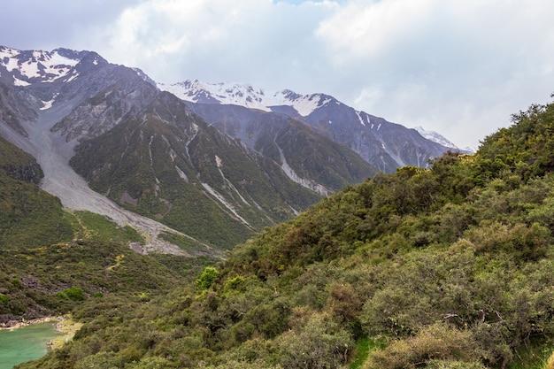 Заснеженные скалы над следами ледника голубого озера возле озера тасман, новая зеландия