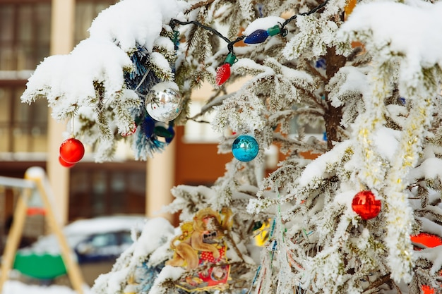 Snowcovered branches of a christmas tree with bright winter toys outdoor closeup