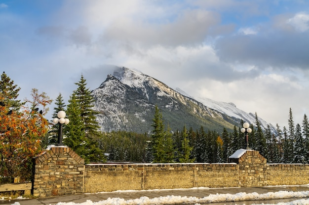 Snowcovered mount rundle mountain range with snowy forest over blue sky and white clouds in winter