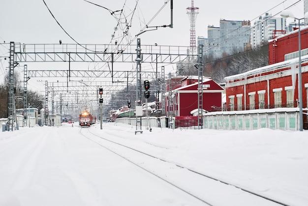 Заснеженный вокзал со старинными мастерскими и прибывшим составным поездом i