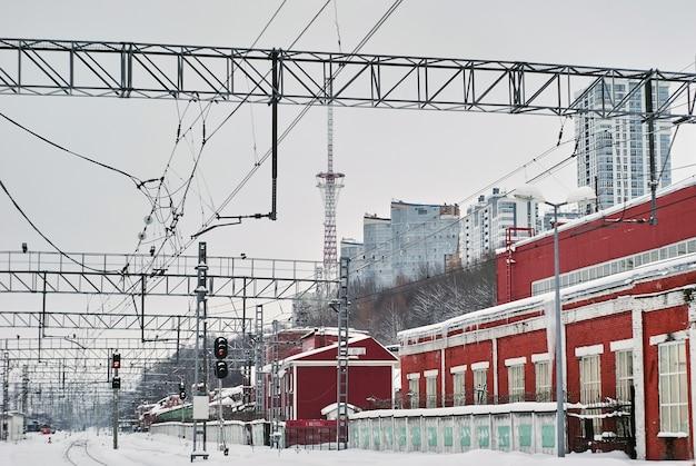 Заснеженный вокзал со старинными мастерскими на переднем плане