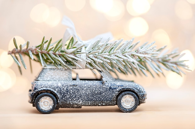 Snowcovered toy car with a christmas tree on a bokeh background christmas concept