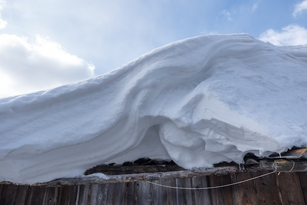 Snowdrift on the roof against the blue sky with clouds closeup snowdrift after a blizzard