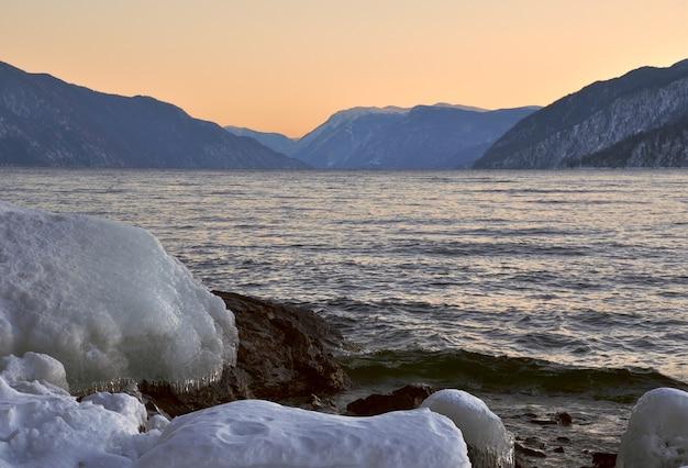 テレツコイ湖のほとりの雪の吹きだまりと氷が冬の山で凍っていない
