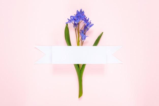 白いリボンとピンクの背景にスノードロップの花