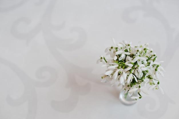 白い光沢の上に花瓶でスノードロップの花