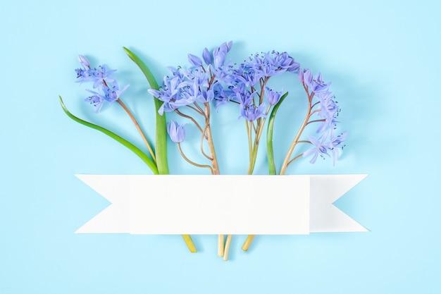 白いリボンと青い背景のスノードロップの花