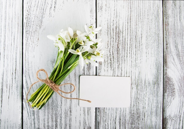 Snowdrops flowers with card on a wooden table