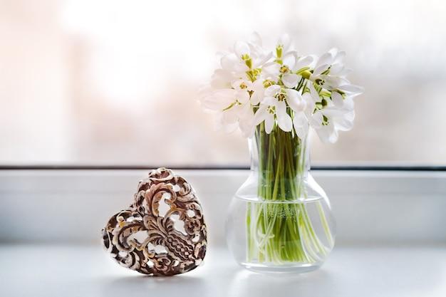 装飾的なハート型の錠が付いている窓のそばの花瓶のスノードロップ。バレンタインデーおめでとうのための雰囲気のあるロマンチックな作曲。テキスト用の空き容量