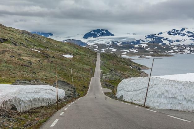 Заснеженная дорога, дорога в норвежских горах в летний сезон