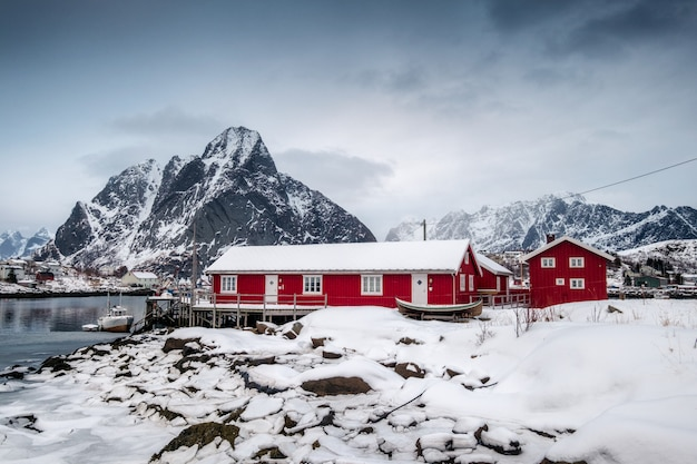 Snowfall on red house with harbor in valley on arctic ocean