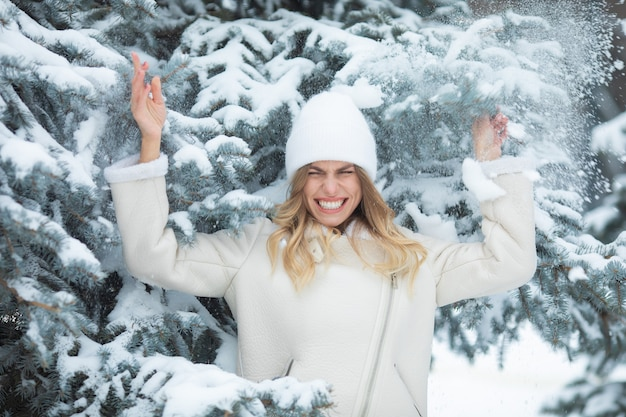 Снегопад. девушке на голову падает снег. улыбающаяся женщина зимой.