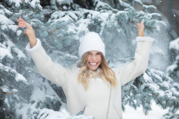 강설량. 소녀의 머리에 눈이 내립니다. 겨울에 웃는 여자.