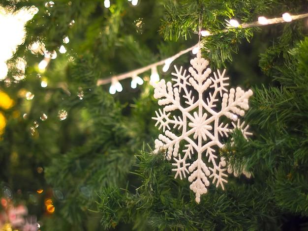 スノーフレークキラキラクリスマスクリスマスツリーの装飾を吊るすクリスマス。