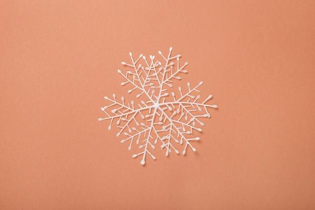 Снежинка на коричневом фоне. концепция на новый год и сочельник. баннер. плоская планировка, вид сверху.