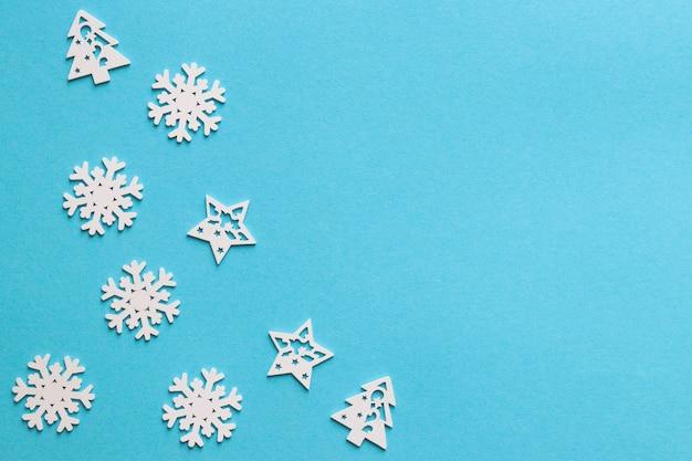 Снежинки, новогодняя елка и звезды на синем новогоднем фоне с копией пространства