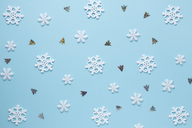 Snowflakes and christmas trees on blue background