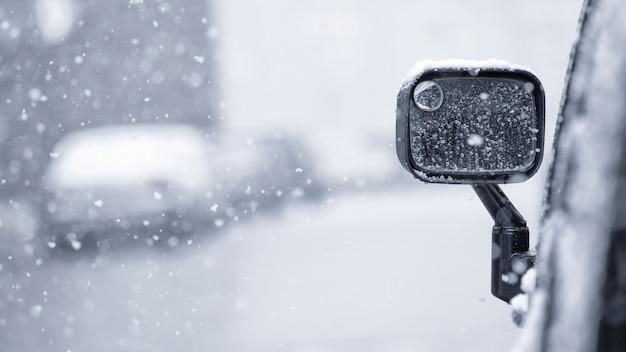 눈송이는 겨울 도시 거리의 자동차 거울에 떨어집니다. 강설 또는 눈보라.