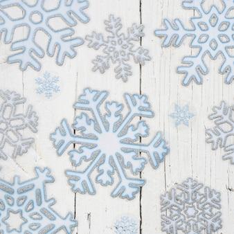 白い木製の背景の上の雪片