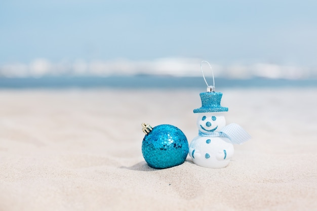 Snowman in a blue hat and blue christmas ball