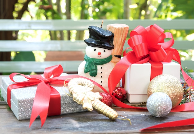 Snowman, christmas present and ornament over wooden table