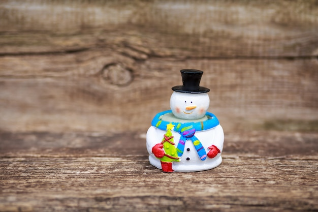 Snowman figure on a wooden table outdoors