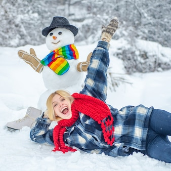 Snowman and funny girl in winter outside. cute snowman at a snowy village.